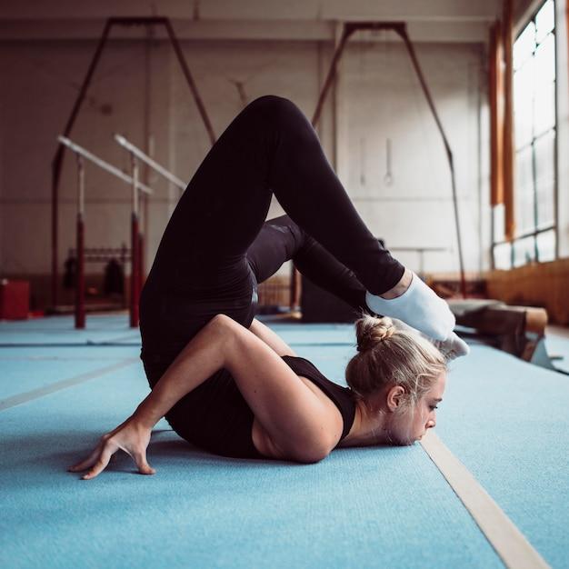 Zijaanzicht jonge vrouw training voor olympische gymnastiek Gratis Foto