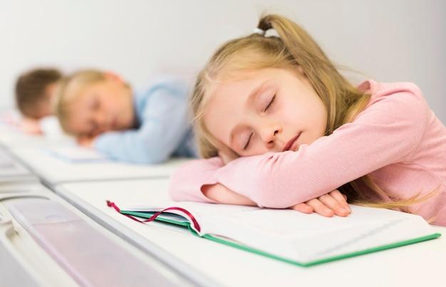 Zijaanzicht kinderen slapen op hun bureau Gratis Foto
