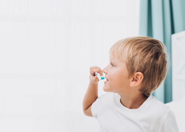 Zijaanzicht kleine jongen zijn tanden poetsen Gratis Foto
