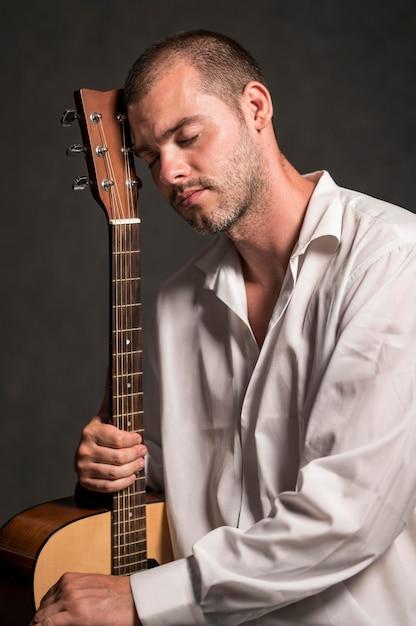 Zijaanzicht man met zijn hoofd op gitaar headstock Gratis Foto
