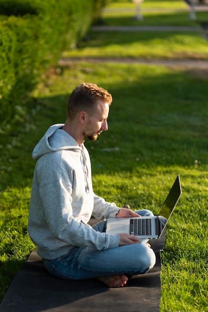 Zijaanzicht man zit in de lotushouding tijdens het werken op laptop Gratis Foto