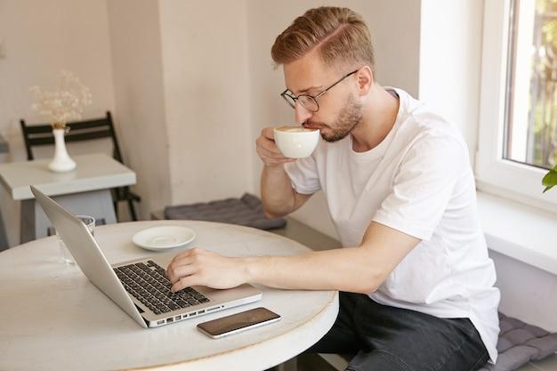 Zijaanzicht met bebaarde mooie man in wit t-shirt, koffie drinken en op afstand werken met laptop in openbare ruimte, kleine pauze maken Gratis Foto