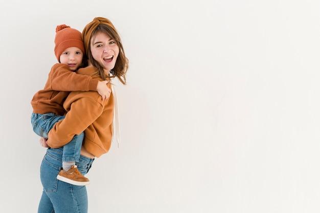 Zijaanzicht moeder met zoon op de rug rit Gratis Foto