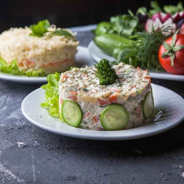 Zijaanzicht olivier salade met mimosa salade en tomaat en komkommer in ronde witte plaat Gratis Foto