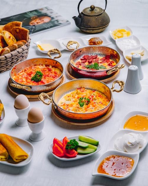 Zijaanzicht ontbijt geserveerd tafel roerei met tomaten met plantaardige omelet omelet met worst in een pan Gratis Foto