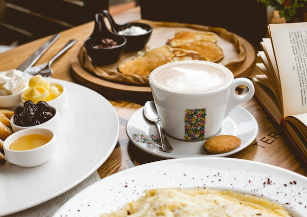 Zijaanzicht ontbijt kopje cappuccino met hapjes en pannenkoeken met jam Gratis Foto