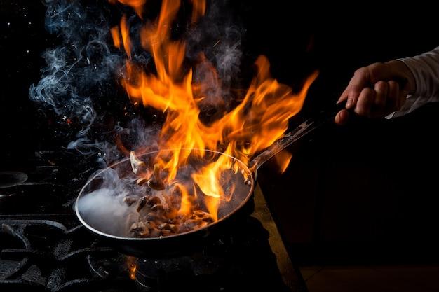 Zijaanzicht paddestoel bakken met fornuis en vuur en menselijke hand in pan Gratis Foto
