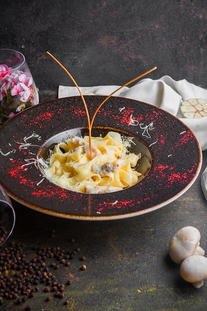 Zijaanzicht paddestoel pasta met champignon en zwarte peper korrels in ronde plaat Gratis Foto