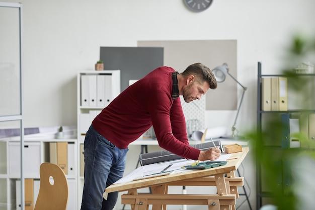 Zijaanzicht portret van bebaarde architect blauwdrukken tekenen terwijl leunend op bureau op de werkplek, Premium Foto