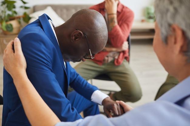 Zijaanzicht portret van rouwende afro-amerikaanse man huilen in steungroep met volwassen vrouw hem troosten, kopie ruimte Premium Foto