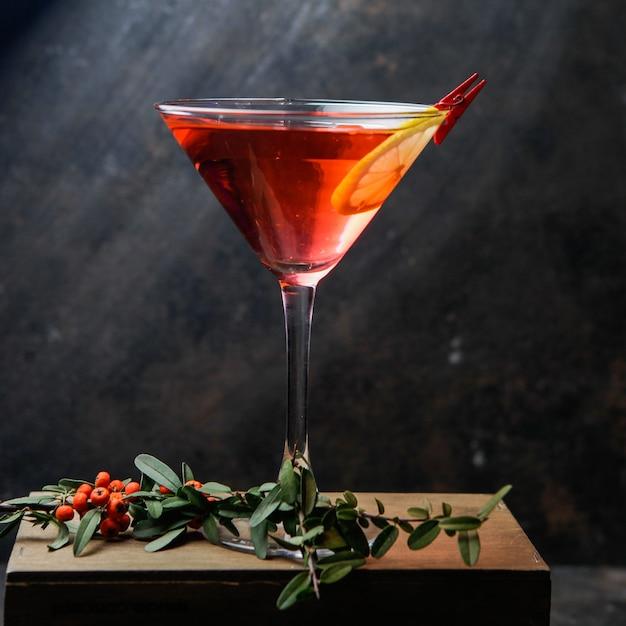 Zijaanzicht rode martini cocktailglas met citroen en rode bessen Gratis Foto