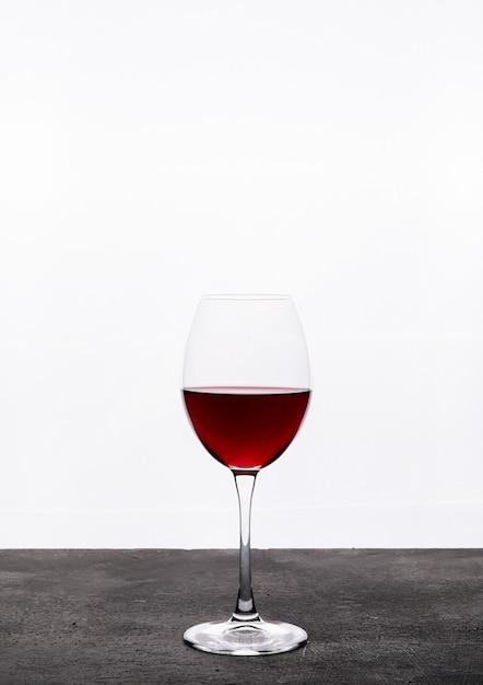 Zijaanzicht rode wijn in glas op witte verticaal Gratis Foto