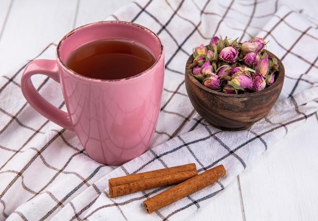 Zijaanzicht roze kopje thee met kaneel en gedroogde bloemen op een geruite witte handdoek Gratis Foto