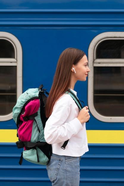 Zijaanzicht schattig meisje op het treinstation met rugzak Gratis Foto