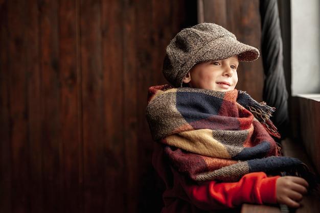 Zijaanzicht schattige jongen met muts en sjaal Gratis Foto