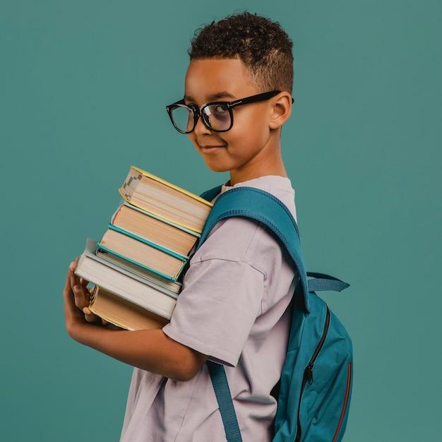 Zijaanzicht schooljongen met een stapel boeken Premium Foto