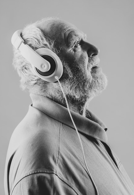 Zijaanzicht senior met koptelefoon Gratis Foto