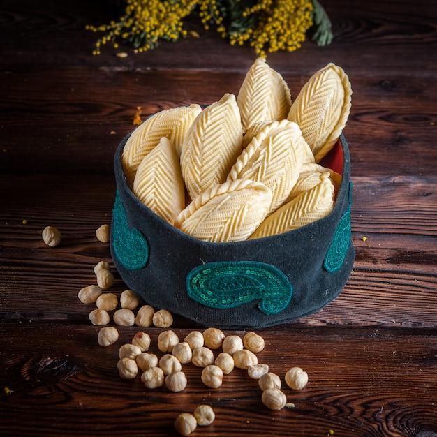 Zijaanzicht shekerbura met noten en mimosabloemen in nationale hoed op houten lijst Gratis Foto