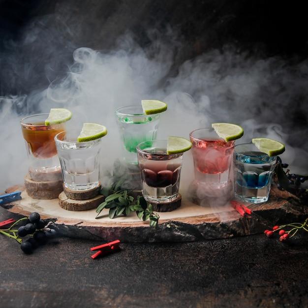 Zijaanzicht shot glazen met kleur drankjes en limoen Gratis Foto