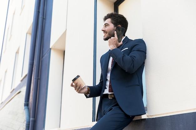 Zijaanzicht smiley advocaat praten via de telefoon Gratis Foto