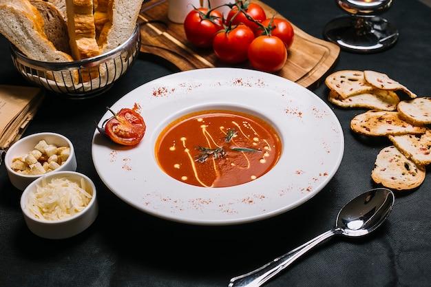 Zijaanzicht tomatensoep met kaas en crackers Gratis Foto