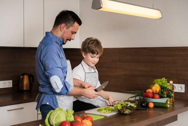 Zijaanzicht vader en zoon groenten snijden Gratis Foto