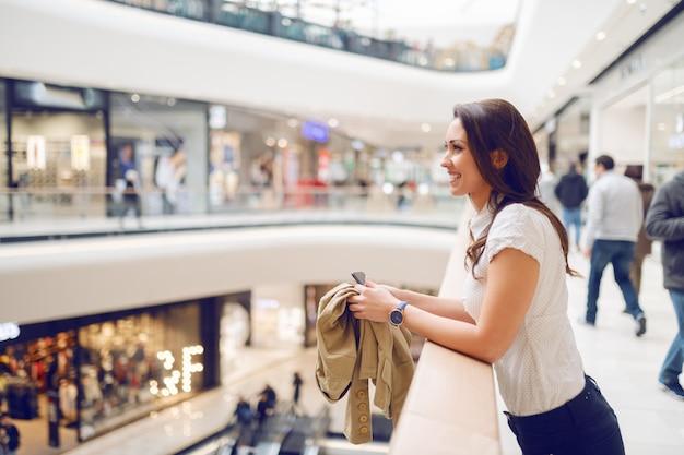 Zijaanzicht van aantrekkelijk brunette die op traliewerk leunen en jasje en slimme telefoon houden terwijl het genieten van van haar tijd in winkelcomplex. Premium Foto