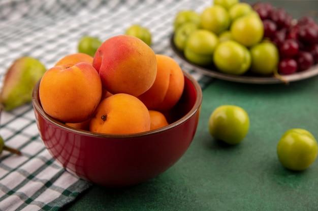 Zijaanzicht van abrikozen in kom en pruimenkersen in plaat met peer op geruite doek en groene achtergrond Gratis Foto