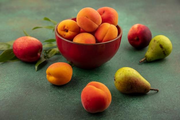 Zijaanzicht van abrikozen in kom met patroon van perziken, peren en abrikozen op groene achtergrond Gratis Foto