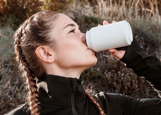 Zijaanzicht van atletische vrouw frisdrank drinken Gratis Foto