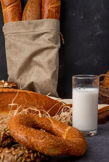 Zijaanzicht van bagel en glas melk met zak stokbrood op kastanjebruine oppervlakte en zwarte achtergrond met exemplaarruimte Gratis Foto