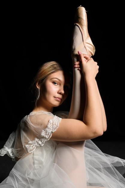 Zijaanzicht van ballerina in het uitrekken van de tutu kleding been Gratis Foto