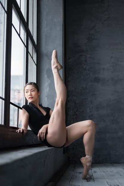Zijaanzicht van ballerina in maillot het stellen door het venster met omhoog been Gratis Foto