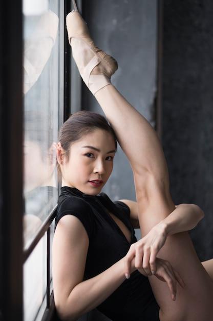 Zijaanzicht van ballerina poseren met been omhoog Gratis Foto