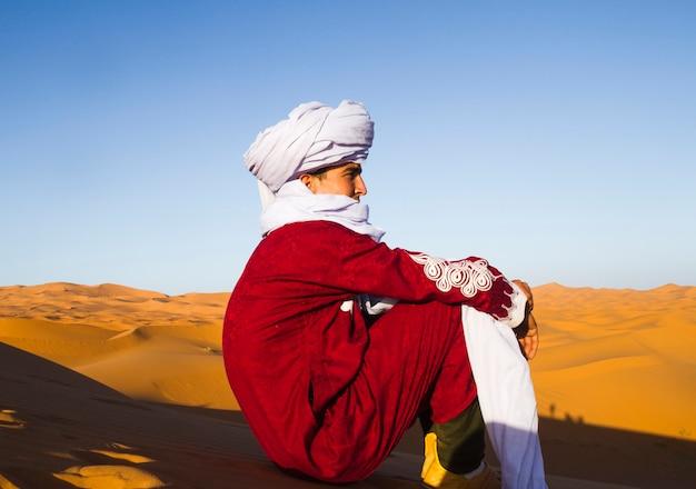 Zijaanzicht van bedouin die in de afstand kijkt Gratis Foto