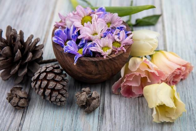 Zijaanzicht van bloemen en pinecones op houten achtergrond Gratis Foto