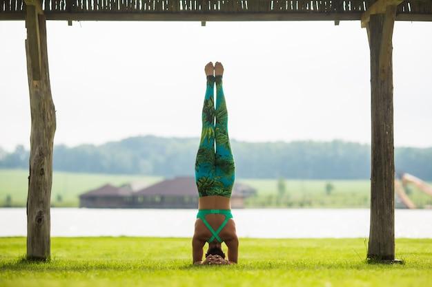 Zijaanzicht van blote voeten jonge geconcentreerde vrouw doet handstand in park in zomerdag Gratis Foto