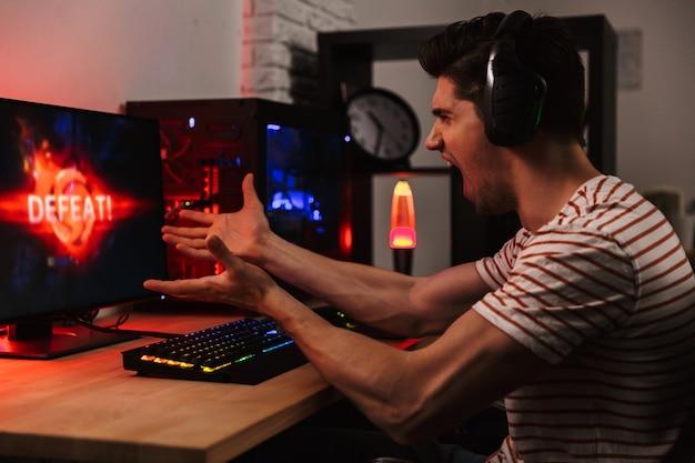 Zijaanzicht van boze gillende gamer die videospelletjes speelt Premium Foto