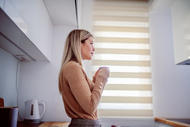 Zijaanzicht van charmante kaukasische blonde jonge vrouw leunend op het aanrecht en thuis genieten van koffie in de ochtend. Premium Foto
