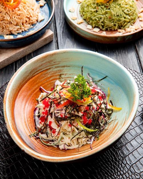 Zijaanzicht van chinese salade met gehakte koolgroene paprika's en zeekool die met rode kaviaar op een plaat wordt verfraaid Gratis Foto