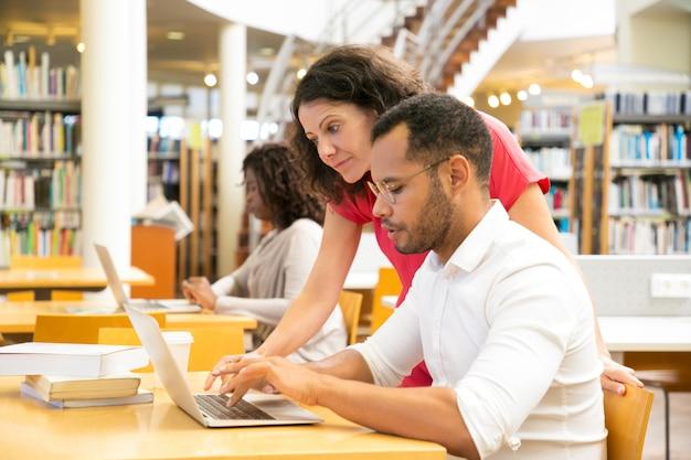 Zijaanzicht van collega's die met laptop bij bibliotheek werken Gratis Foto