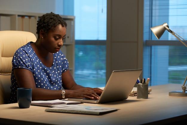 Zijaanzicht van cubaanse vrouw die e-mails op het werk in de avond beantwoordt Gratis Foto