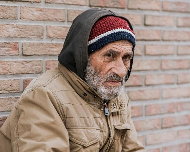 Zijaanzicht van dakloze man buiten Gratis Foto