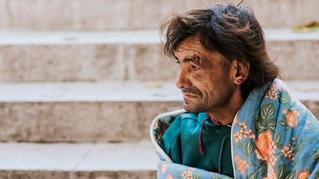 Zijaanzicht van dakloze man buitenshuis met deken naast trappen Gratis Foto
