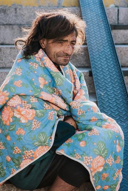 Zijaanzicht van dakloze man buitenshuis met deken Gratis Foto