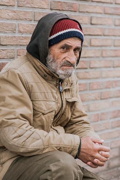 Zijaanzicht van dakloze man buitenshuis Gratis Foto