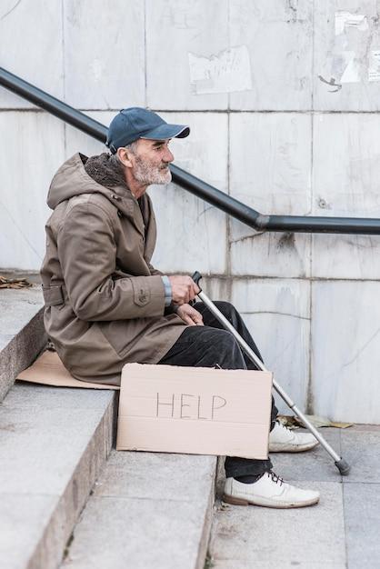 Zijaanzicht van dakloze man op trappen met stok en help-teken Gratis Foto