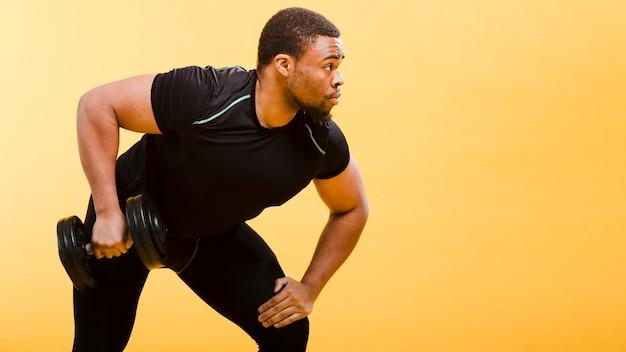 Zijaanzicht van de atletische gewichten van de mensenholding Gratis Foto