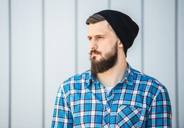 Zijaanzicht van de bebaarde man in hoed buiten. Premium Foto
