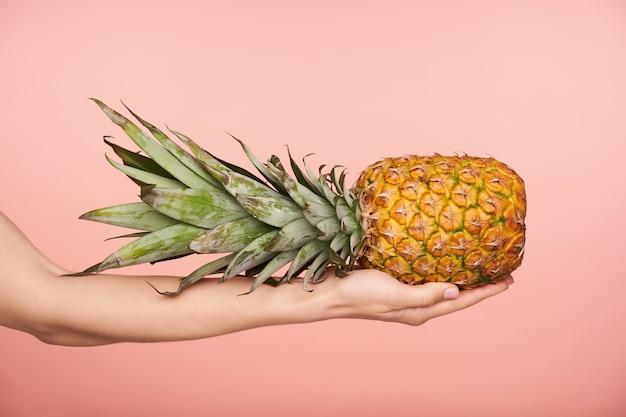 Zijaanzicht van de hand van de mooie vrouw met naakt manicure die grote verse ananas houdt terwijl wordt geïsoleerd op roze achtergrond. menselijke handen en voedselfotografie Gratis Foto